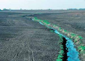 ditch or stream running through a farm field