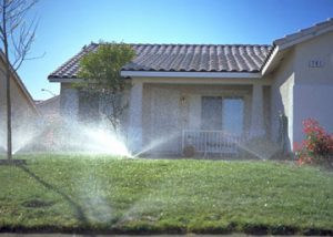 front yard of home being irrigated with sprinkler system