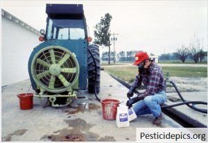 man mixing pesticides over a concrete pad